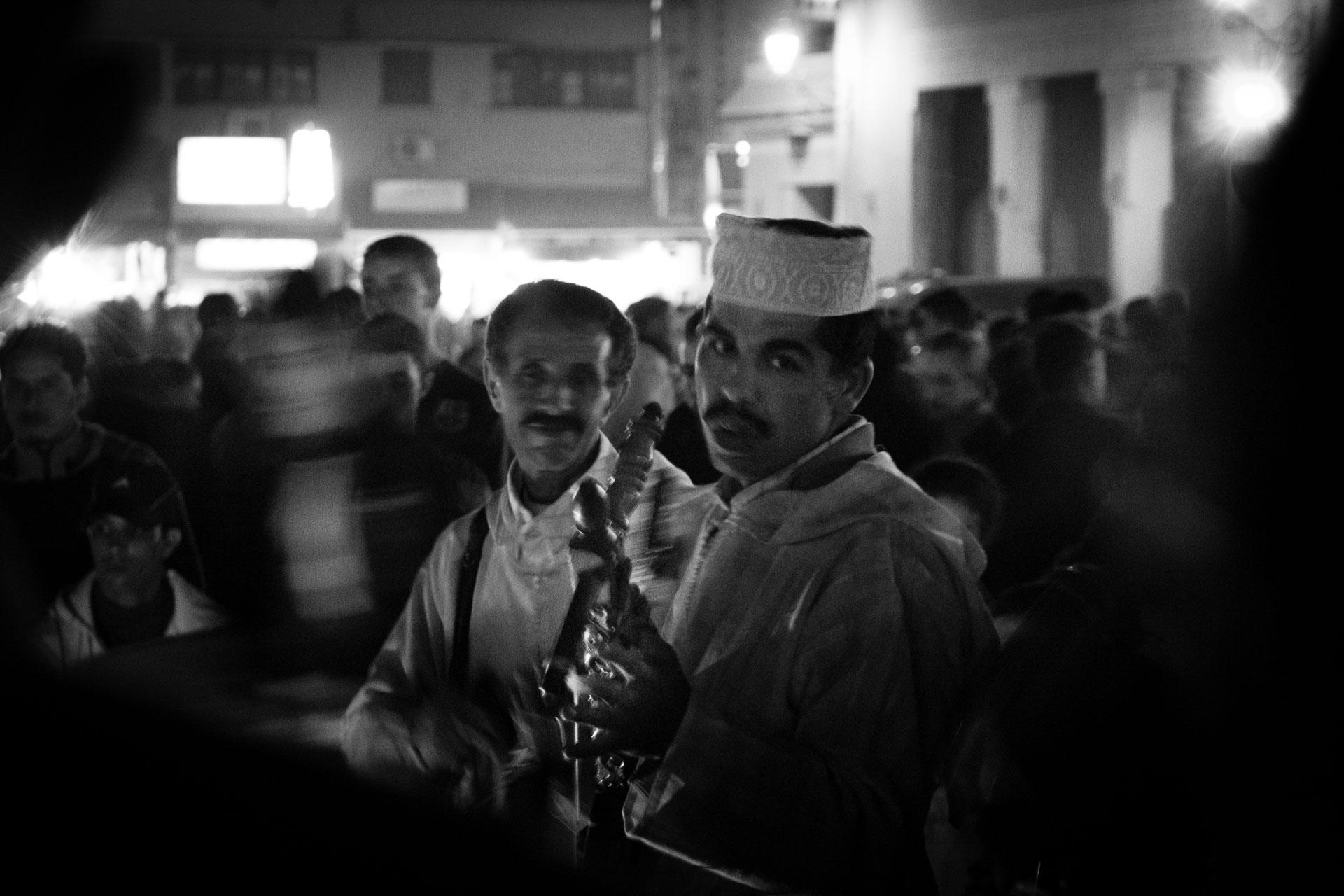 Fotografía en blanco y negro donde dos músicos árabes tocan sus instrumentos