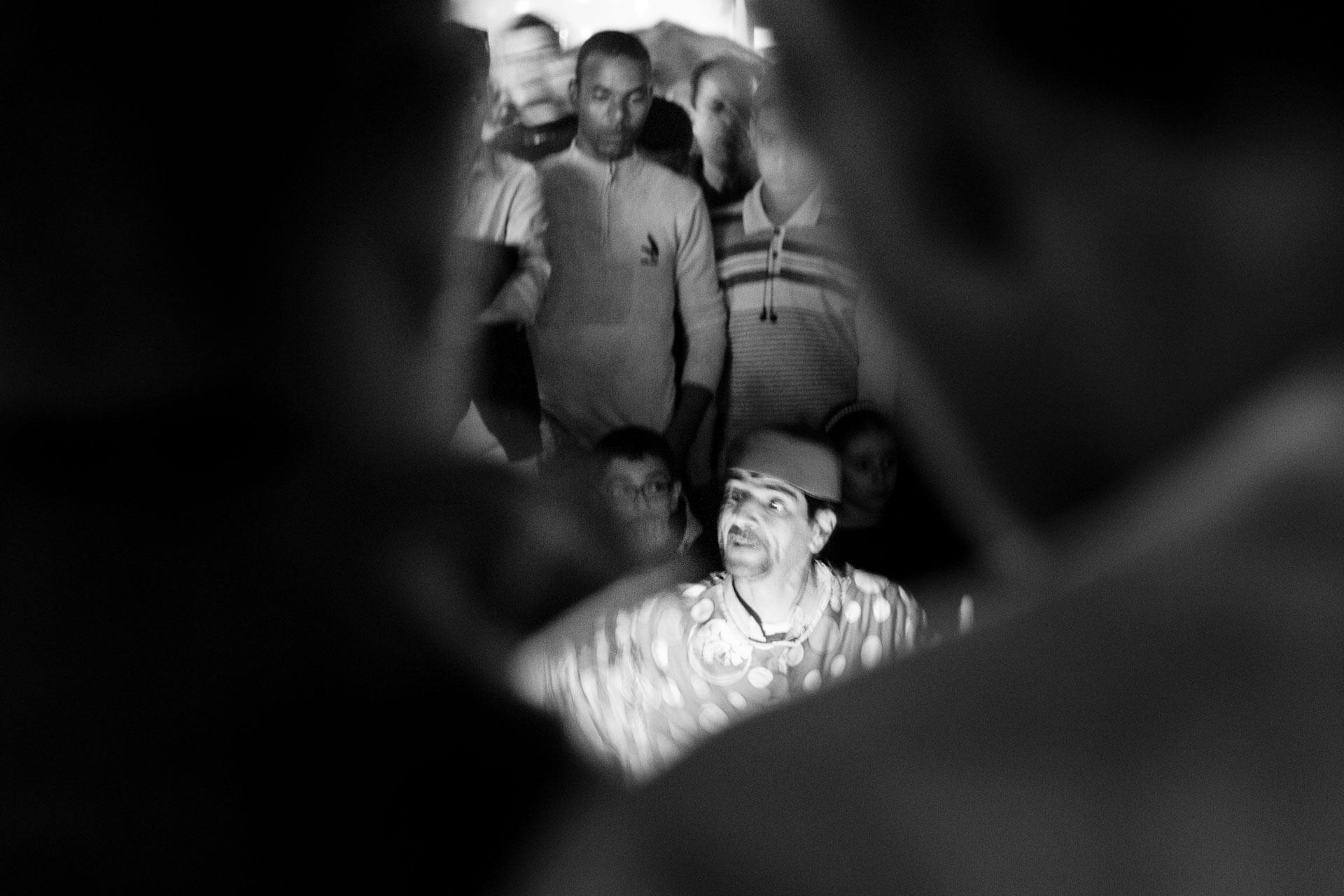 Fotografía en blanco y negro donde un grupo de gente rodea a un contador de historias en la página de Jamaa el Fna en Marruecos