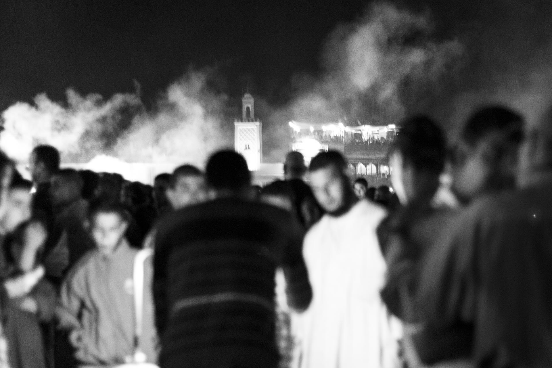 Fotografía en blanco y negro donde se ve un grupo desnefocado en la plaza Jamaa el Fna en Marruecos
