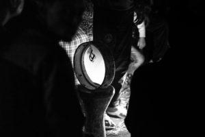 Imagen de una pandereta iluminada por luz artificial en medio de un grupo de gente