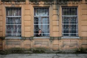 Mujer encerrada en casa mirando por una ventana enrejada en Kutaisi, Georgia.
