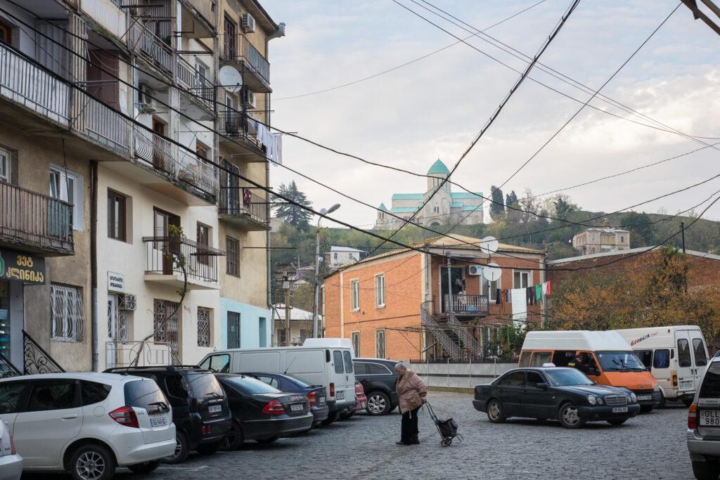 Mujer volviendo de hacer la compra en Kutaisi con la catedral de fondo