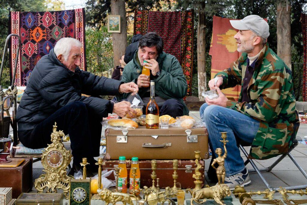 Grupo de gente bebiendo y comiendo en un mercado local urbano en Tbilisi