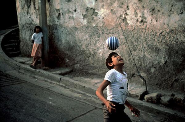 Niño jugando en la calle con una pelota