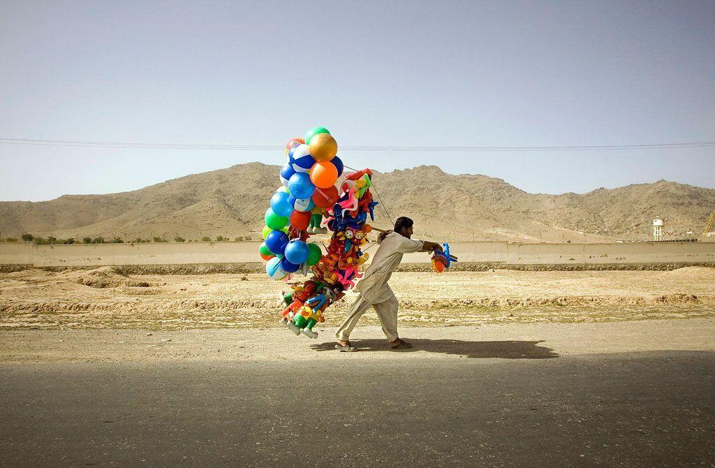 hombre caminando con globos bajo una luez dura en el desierto en Afganistan