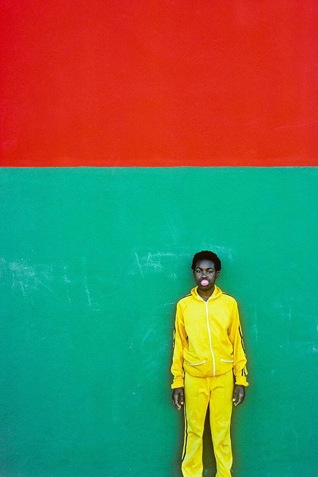 Retrato de un joven con chandal amarillo en una pared verde y naranja de Jay Maisel que ejemplifica la importancia de los colores en la fotografía