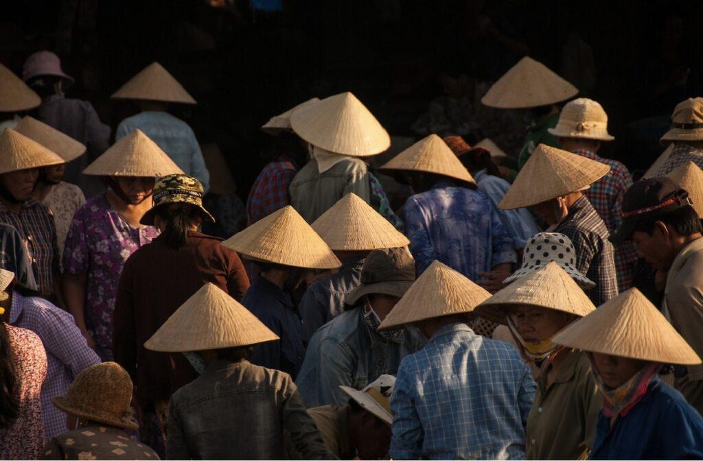 La luz lateral baña los sombreros típicos de un mercado asiático