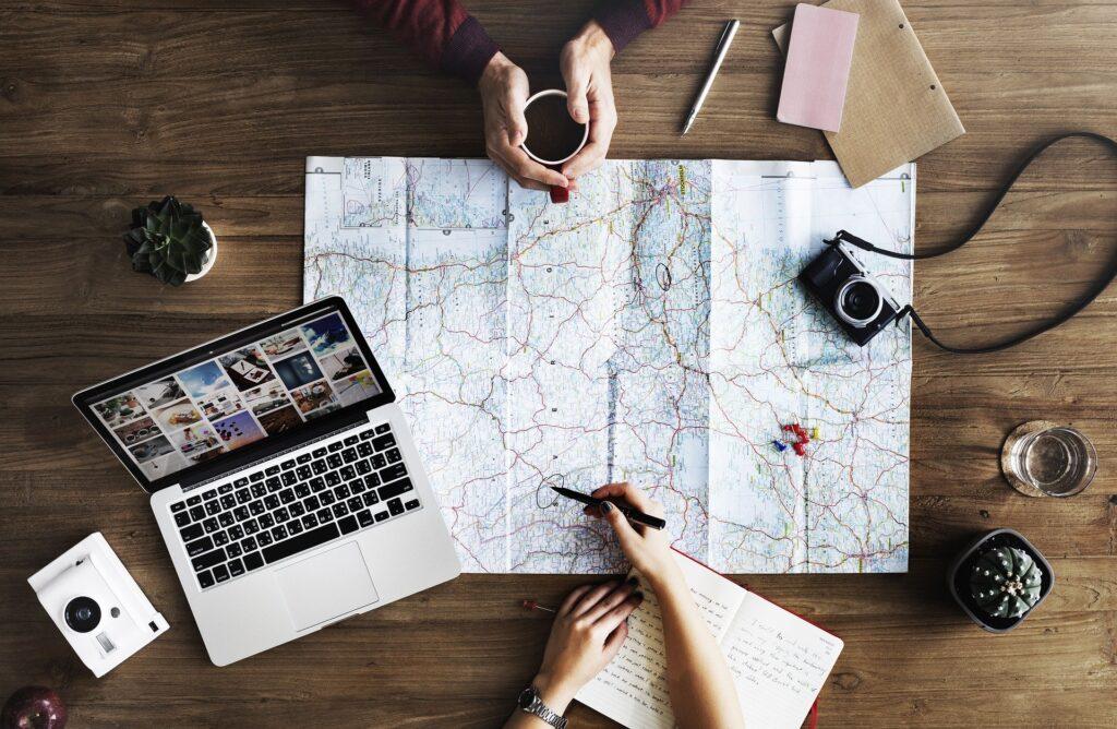 una pareja planea un viaje con mapas ordenadores una cama y una libreta de apuntes.