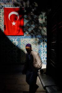 Hombre pasa por delante de una pared azul con una bandera de Turquía