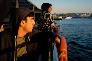 Chico y chica en Ferry en el Cuerno de oro en Estambul