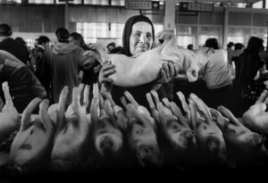 Mercado en Georgia donde una mujer tiene en brazos un cochinillo. Cristina García Rodero.