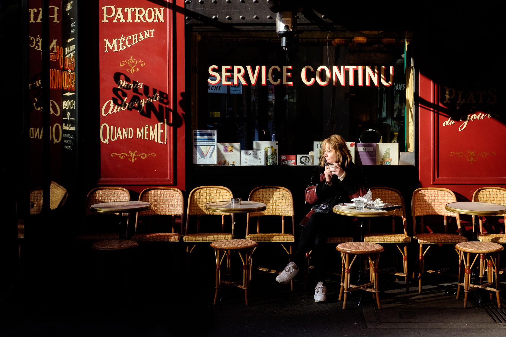 Mujer en cafetería de París como ejemplo de Consejos de fotografía y viajes